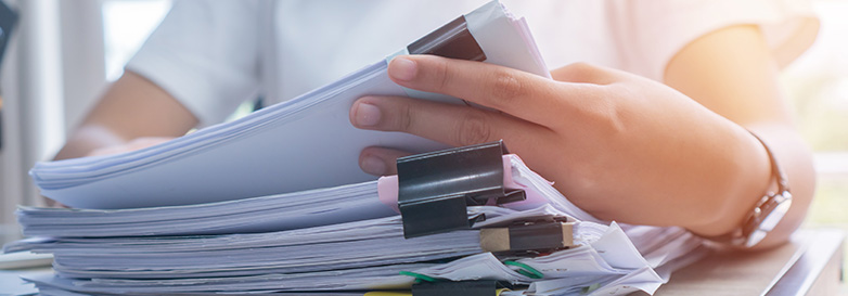 Business Documents concept : Employee woman hands working in Stacks paper files for searching